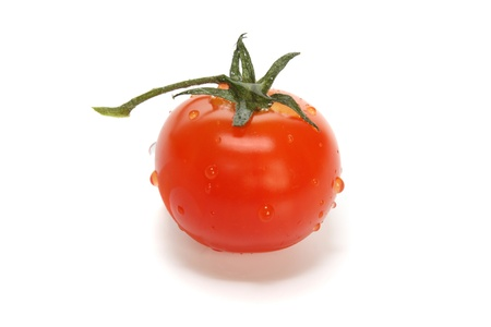 Ripe tomato of cherry in drops on a white background