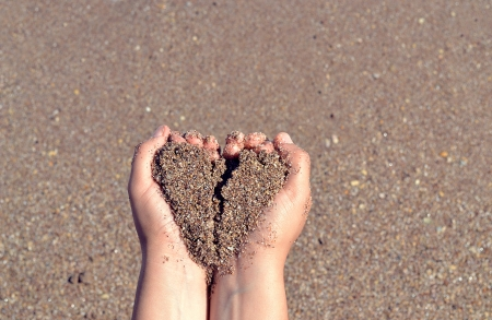 heart on the sand: sand in hands with heart shape