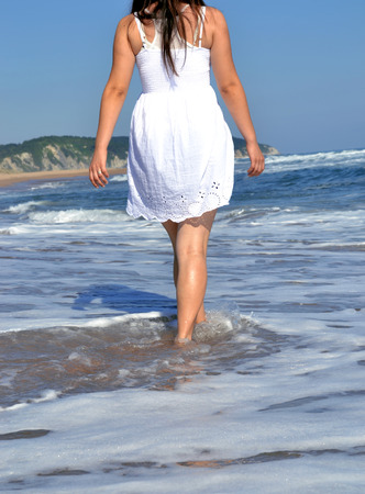 esc: A woman walking on the beach Stock Photo