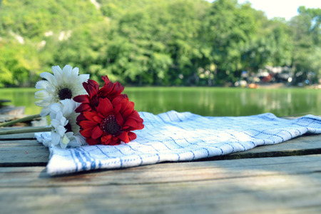 Empty wooden deck table with tablecloth over bokeh