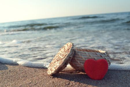 Red heart on white sand beach photo