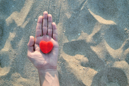 consoling: Hand holding a heart. Stock Photo