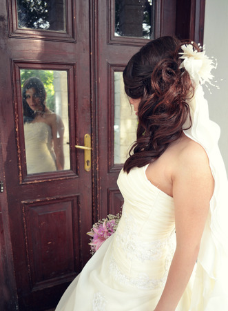 Elegant in the mirror Reflection of a Beautiful bride in a modern glass building penthouse Stock fotó