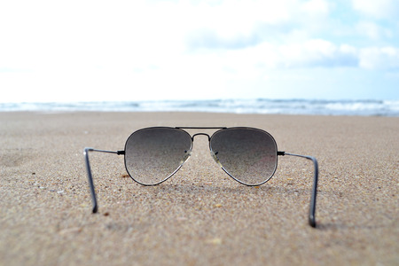 sunglasses on the beach; view of the sea through dark sunglasses on shells