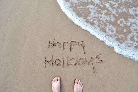 happy holidays: Happy holidays sign on the beach sand Stock Photo