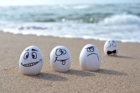 funny eggs on white sand beach over blue sea, happy easter or summer holiday concept. Stock Photo