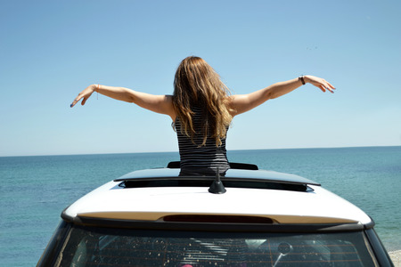sunroof: Joyful woman waving on summer vacation car travel to the coast. Brunette girl having fun sunroof vehicle leaning out towards the sea.