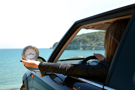 Rear view of relaxed woman on summer travel vacation to the coast towards the sea leaning out car windows Stock fotó