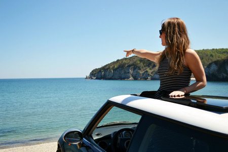 sunroof: Relaxed happy woman on summer travel vacation to the coast leaning out the car sunroof with the sea on background. Stock Photo