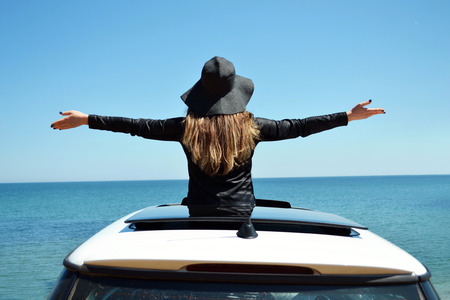 sunroof: Rear view of relaxed woman on summer travel vacation to the coast towards the sea leaning out the car sunroof