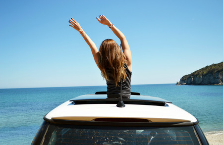 Joyful woman waving on summer vacation car travel to the coast. Brunette girl having fun sunroof vehicle leaning out towards the sea