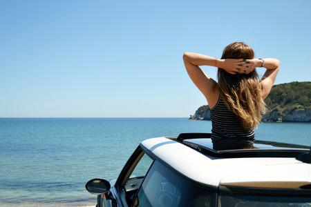 Achteraanzicht van ontspannen vrouw op de zomer vakantie aan de kust in de richting van de zee leunend uit de auto zonnedak.
