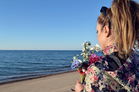 Young beautiful smiling woman smells small bouquet of colorful florets, against summer sea Stock fotó