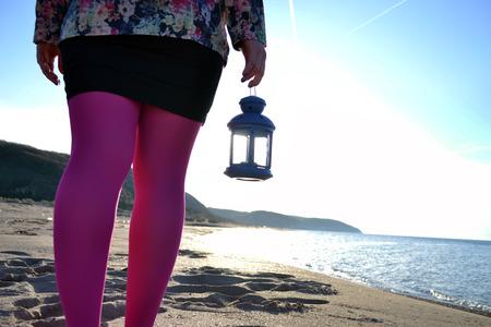 oil lamp: Full length young woman with oil, kerosene lamp on pier