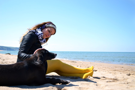 unhappy woman sitting on the beach with the dog