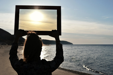 Beautiful woman holding an empty frame Stock fotó