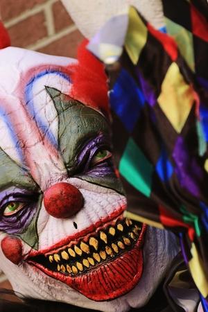 guadaña: Cierre de Halloween del payaso de terror partido. El payaso de pie miedo