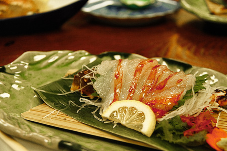 Correct authentic Crab sashimi dish plate unique to Japan.Japanese food style with Crab sashimi with green leaves-cinematic color in film style with flare light