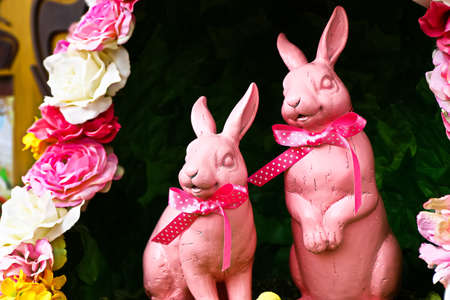 Color of Pink Easter rabbit for decoration on green grass. Happy Easter card with copy space. Easter bunnies on green grass.