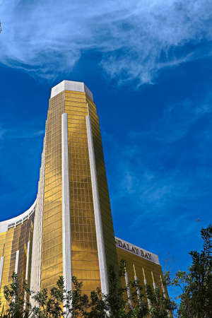 Las Vegas, NV/USA-Sep 15, 2018; Enormous Mandalay Bay Hotel Resort and Casino Las Vegas with beautifully landscaped entrance to modern architectural gold Glass facade of building.