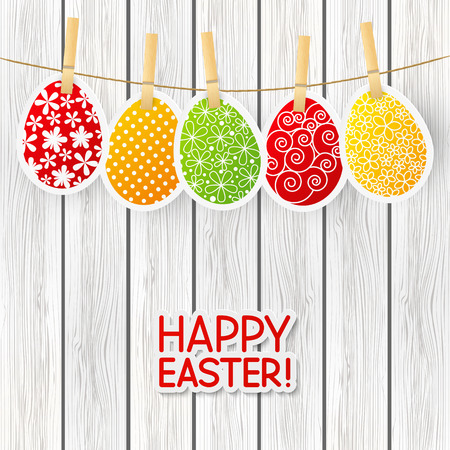 clothespin and rope: Paper Easter eggs on wooden background