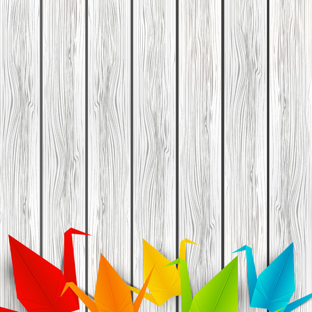 Paper origami cranes on wooden background Vectores