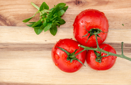 Tomates and basil on a wooden board. top down view