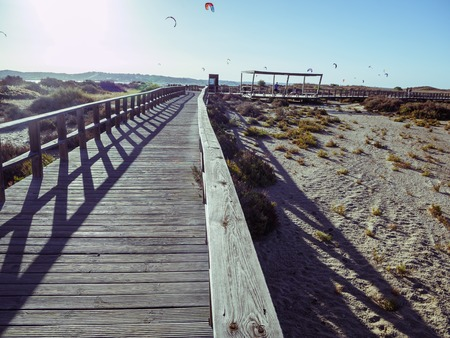 Wooden pier with kite surfers, the sun and beach in the background 写真素材
