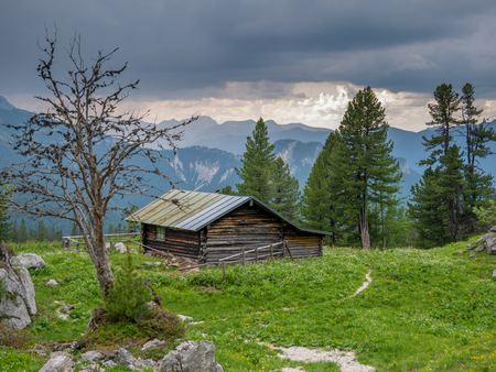 Wooden cabin in the bavarian alps near the Schachenhaus with stormy weather in the background