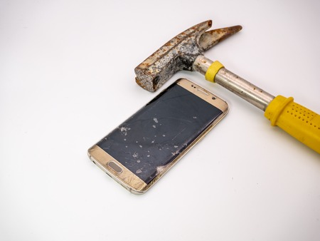 damaged smartphone disply with hammer next to it
