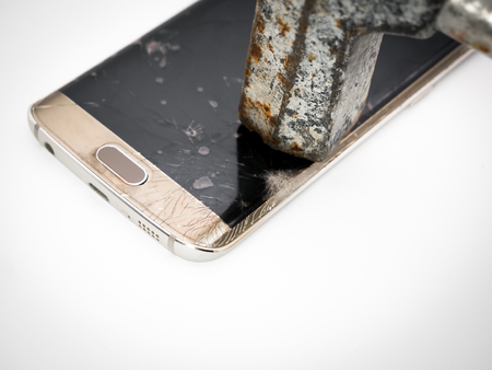 close-up of damaged smartphone display with hammer and white background Banco de Imagens