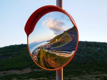 Round traffic mirror reflecting street and city