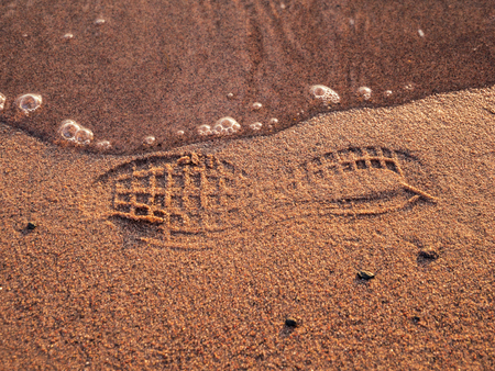 footprint of a shoe on a beach with water