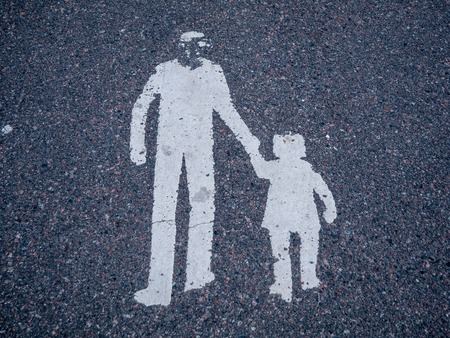 Sign of man and children on asphlat