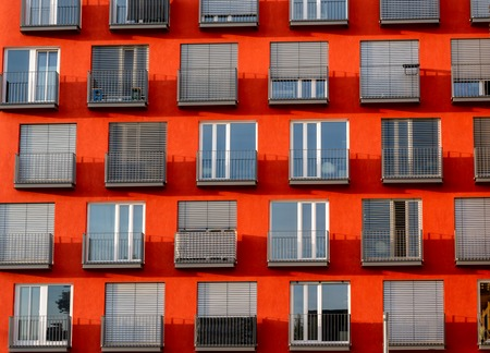 Close up image of red high rise building with windows and balconies and blinds
