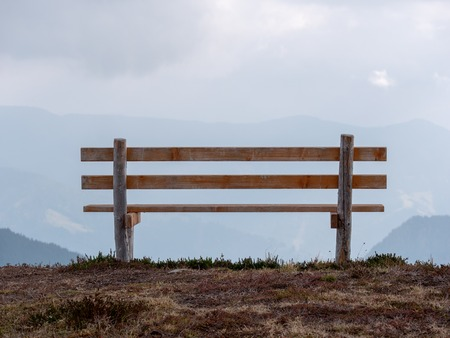 Close up image with focus of bench with mountains in the background