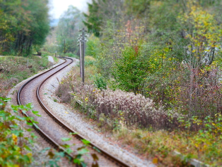 Tilt shift image of winding railroad tracks in autumn