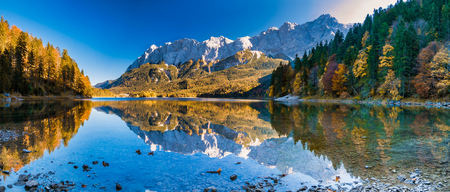 Panorama image of the zugspitze with water reflection in the eibsee during autumn Imagens