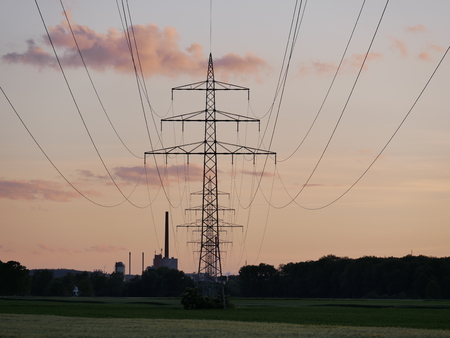 Image of power train line during sun set with power plant pink clouds