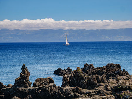 Image from a cliff with a sailing boat in the atlantic and the island of Pico with mountain Pico in the background Azores Portugal Europe