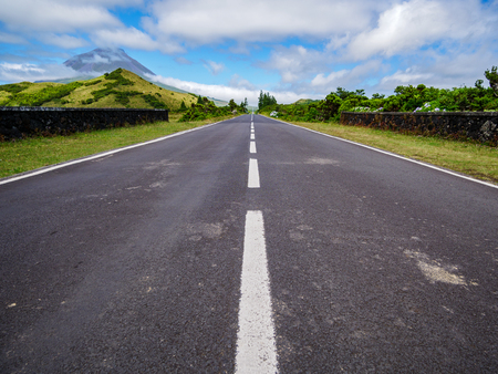 Image of road leading to a avanishing point with the mountain of Pico and vegetation Azores Portugal Europe