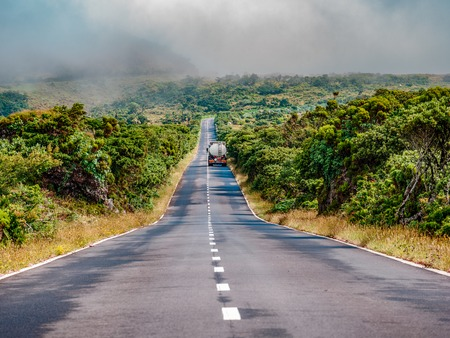 Image of road leading to a avanishing point with the mountain of Pico and vegetation Azores Portugal Europe Reklamní fotografie