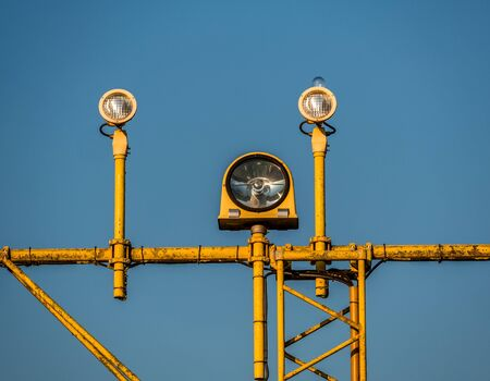Close-up Image of yellow airport signal lights for airplanes with blue sky