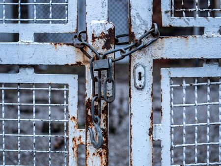 Image of old chain with padlock and white iron gate Stock Photo