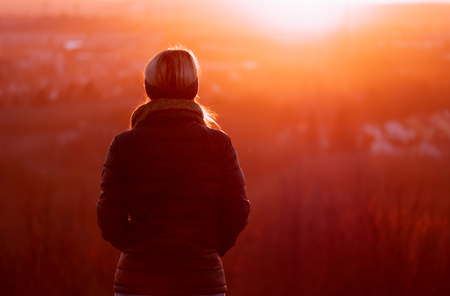 Image of woman from behind looking into the sun during colorful sunset