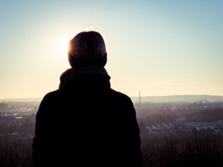 Image of woman from behind looking into the sun during day time Stockfoto