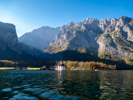 Image of the Koenigssee with the chapel of st bartholomew and a tourist boat. In the background the illuminated mountain formation of Watzmann in bavaria, Germany Archivio Fotografico