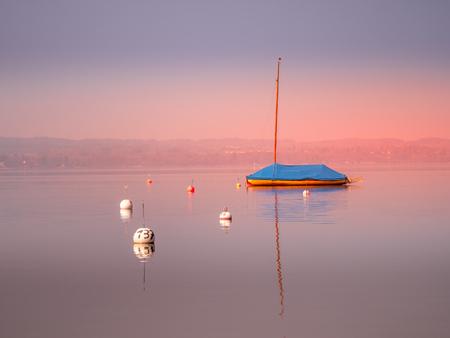Bild eines eingemotteten Segelbootes auf einem See mit Wasserreflexionen bei Sonnenuntergang auf dem Ammersee, Bayern, Deutschland