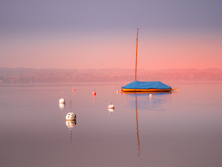 Image of mothballed sailing boat on a lake with water reflections during sunset on lake Ammer, Bavaria, Germany 写真素材