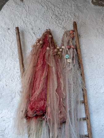 Image of colorful old and used fisher nets hanging on the wall Foto de archivo